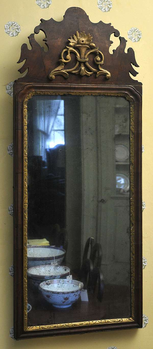 """An 18th C. Queen Anne walnut wall mirror with applied carved floral cartouche, crested with bird effigy with a wonderful old finish. 39""""H."""