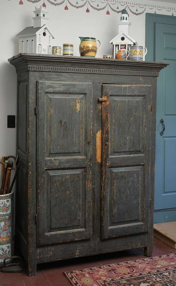 """An 18th C. Canadian two door floor cupboard with thumb nail chip carved cornice raised panel door in old blue paint, 45""""W x 69""""H."""
