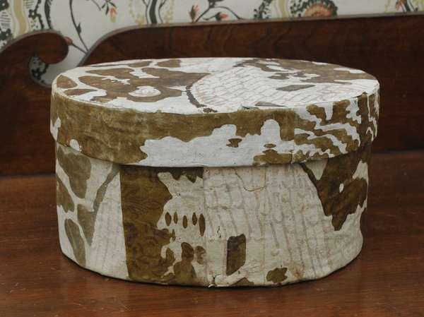 "A circular wall paper on wood banding hat box labeled Hannah Davis, Jaffrey, New Hampshire, 6""H. x 10""L."