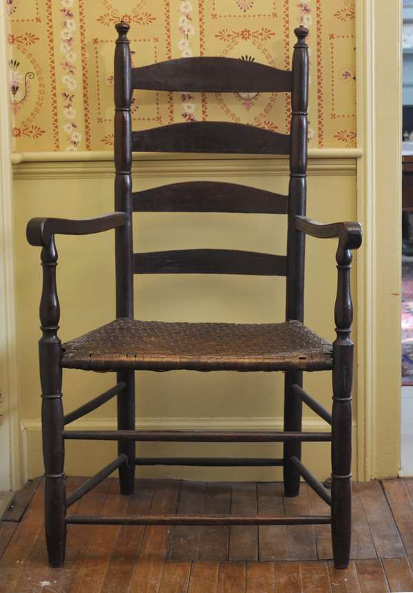 """A late 18th C. New England ladder back arm chair with sausage turnings and early splint seat and an old Spanish brown paint 17"""" seat height, 42""""H"""