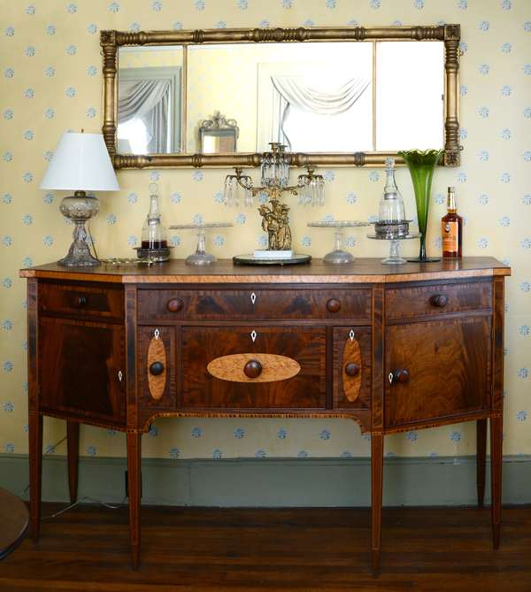 """A fine New Hampshire Federal mahogany side board with oval and banded birdseye maple veneers on a delicate double tapered leg, ca. 1800-1820. Page history states made in Haverhill or Bath around 1816 for Ira Goodall, a lawyer 70""""L. x  41""""H. x 24""""D."""