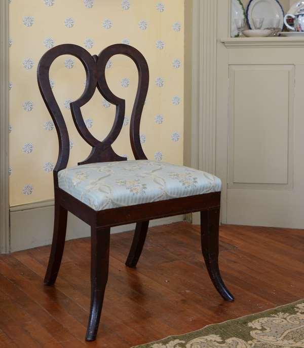 Matched set of six Classical mahogany dining chairs with shield design, scrolled back on tapered, circular saber legs. Original slip seats, old finish ca.1830