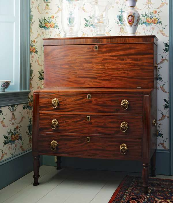 """A Federal New Hampshire two part mahogany drop front ladies secretary with reeded ends and legs, period brass pulls with drop down lid revealing pigeon holes and drawers signed S.A. (Steven Adams working in Haverhill, NH during the early 19th C.) ca. 1820, 42""""L. x 51""""H."""
