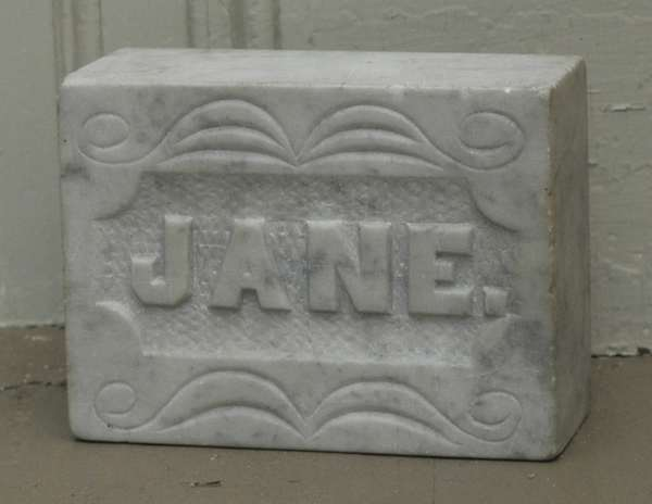 """A 19th C. carved marble doorstop titled """"Jane"""", reverse with Masonic emblem faith, hope, and charity, 4"""" x 6"""""""