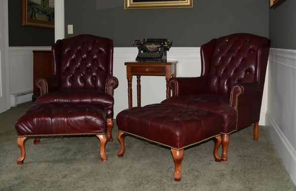 Pair of leather wing chairs with stools (25-43)
