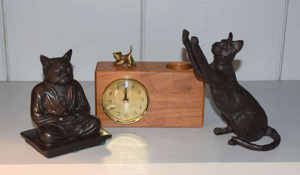 Two bronze cat sculptures along with clock with cat motif, three pieces total