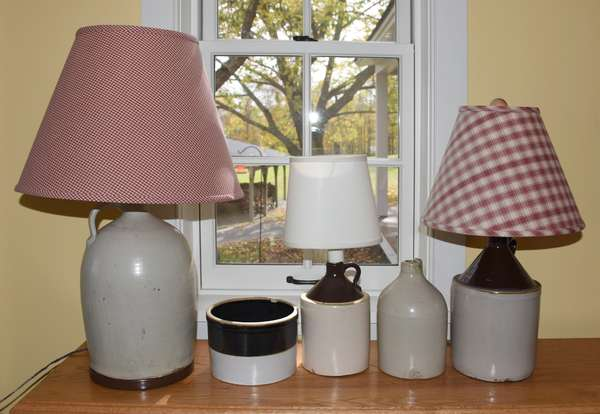 Three stoneware jugs converted to lamps along with other various stoneware pieces, five pieces total