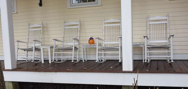 Set of four white painted porch rockers along with three drink tables, seven pieces total