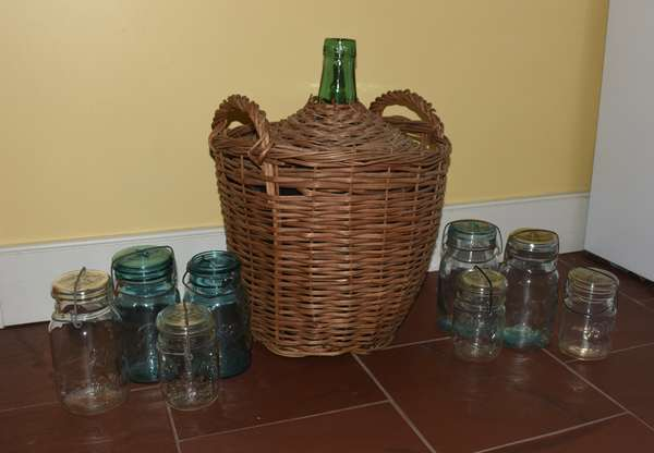 Assortment of old colored canning jars along with demi-john bottle