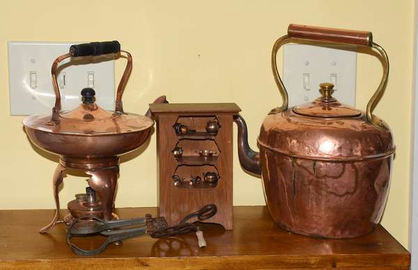 Assembled country lot; two copper kettles along with miniature cupboard with miniature copper accessories along with egg beater
