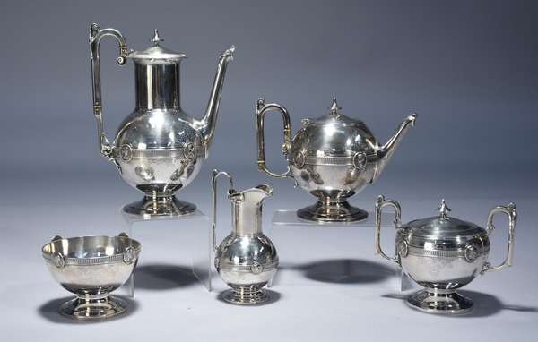 Gorham coin silver.  Five piece Medallion pattern coffee and tea set.  Footed form with medallion placed around mid-waist band, and at terminal of each handle.  Bright cut acanthus leaves and scrolls around the body.  Coffee pot 11