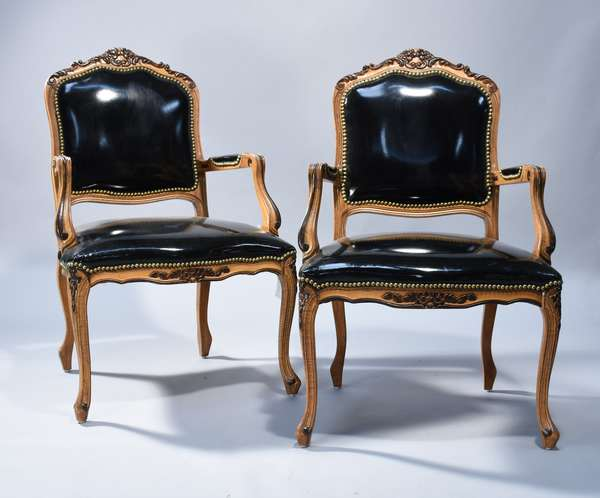 Pair of black leather open armchairs in the Louis XVI style, carved beech frames, 20th C.