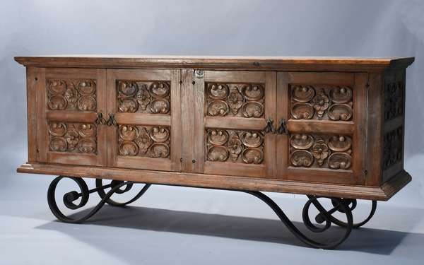 Spanish carved hardwood and wrought iron credenza.  Four doors with carved panels on raised scroll iron base, 76.5