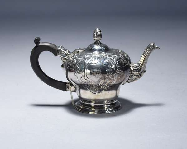 English George II sterling teapot, London 1745 maker Thomas Whipham, of inverted baluster form on stepped foot with chased foliage on shoulders.  Wood handle, artichoke finial, 16 troy oz, 5.25