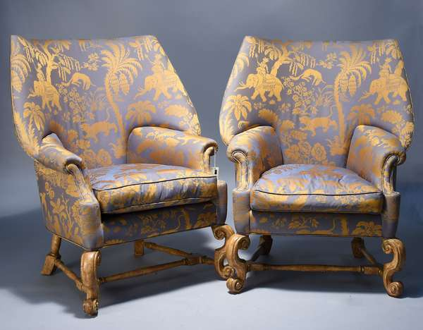 Stylish pair of upholstered wing chairs.  Indian motif silk fabric with elephants, tigers, birds amongst palm trees and trees gessoed  and painted scroll legs and stretchers, 44