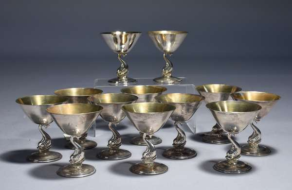 Twelve Mexican sterling Mid-Century figural martini glasses.  Dolphin stem on raised stepped foot, tapered angular bowls with gilt interior, 4