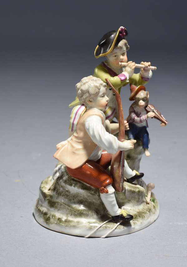 18th C. Vienna porcelain grouping.  Two boys and a monkey are playing instruments while seated on a rock.  7.5