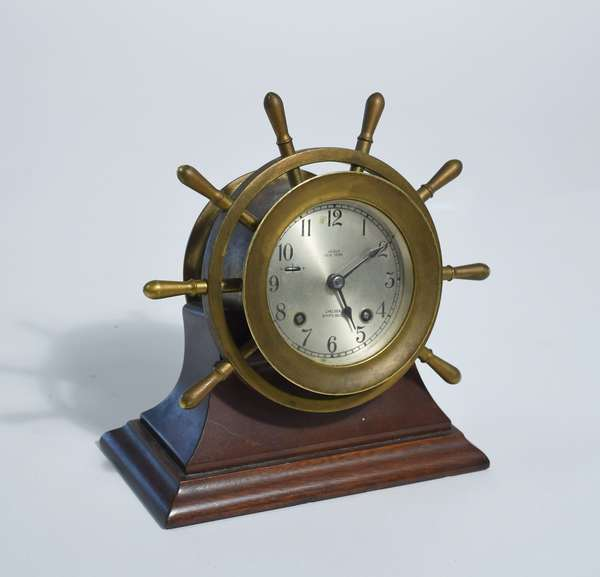 Chelsea ships bell brass wheel form clock with silvered dial, Negus NY, in wood stand, 8.5