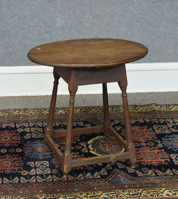 18th C. stretcher base button foot oval top tap table with red stain, 24.5