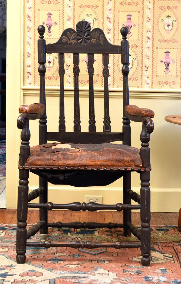 Exceptional 18th C. New England banister back armchair with floral and pinwheel carved crest, old Spanish brown paint with leather arms and seat, 46