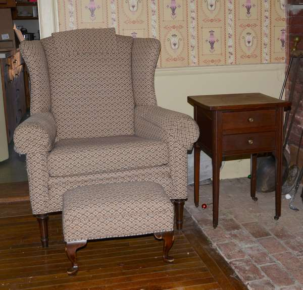 Clean upholstered wing chair with footstool.