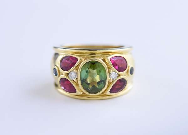 Cartier (C86690) wide multi-stone 18k yellow gold ring set with an oval green tourmaline approx. 1.5 ct, four pink  pear shaped tourmalines (tested) approx. .80 ct tw, approx. .16 ct tw round brilliant cut diamonds and approx. .10 ct tw of blue sapphire cabochons, size 7, 13.2 grams