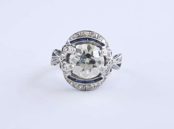 Approx. 3.25 ct Old European cut diamond set into a platinum Edwardian style engagement ring, with approx. .80ct tw diamond and sapphire side stones, approx. size 6, 5.5 grams