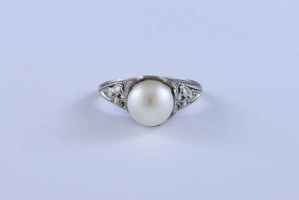 Tiffany & Co. platinum ring set with an 8.63 mm light cream round pearl accented by approx. .36 ct tw round brilliant cut diamonds, size 7.5, 5.5 grams