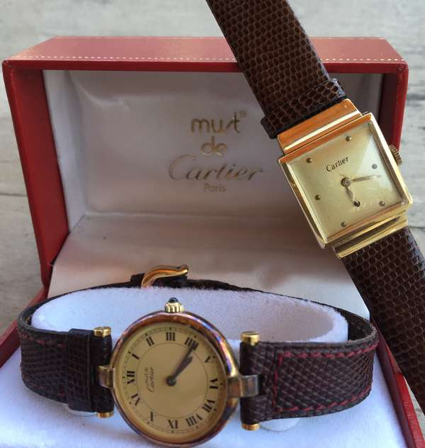 "Two Cartier watches 14k gold with rectangular dial and leather band along with a silver with gold wash ""Must de Cartier with box"