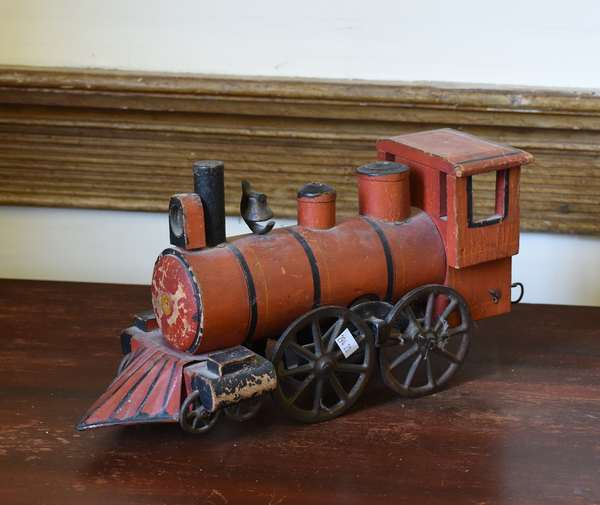Antique wooden toy locomotive in old red paint