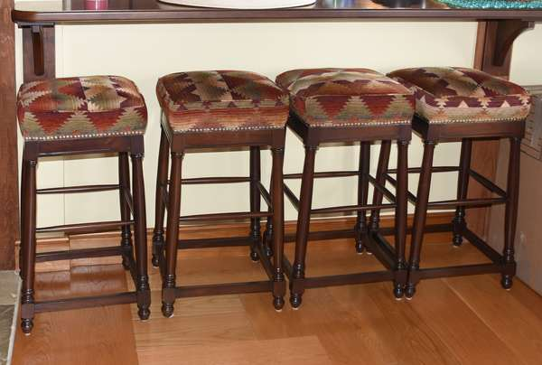 Four upholstered bar stools by Carlos Herrera