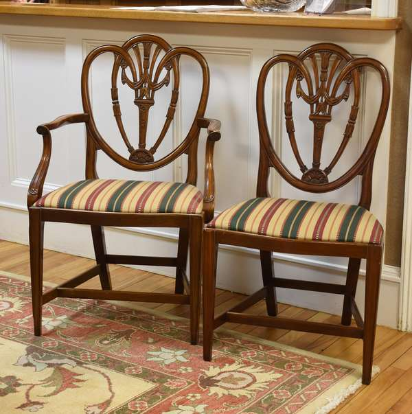 Set of eight carved mahogany shield-back dining chairs, including two arms, c. 1880s