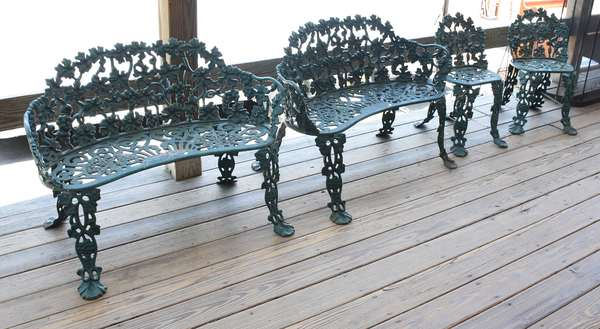 Four piece cast iron garden set in green paint, two settees and two chairs
