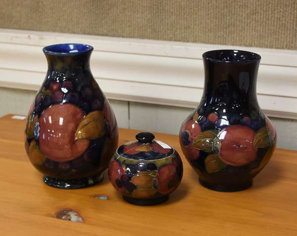 Three piece Moorcroft pomegranate trio, covered pot and two vases
