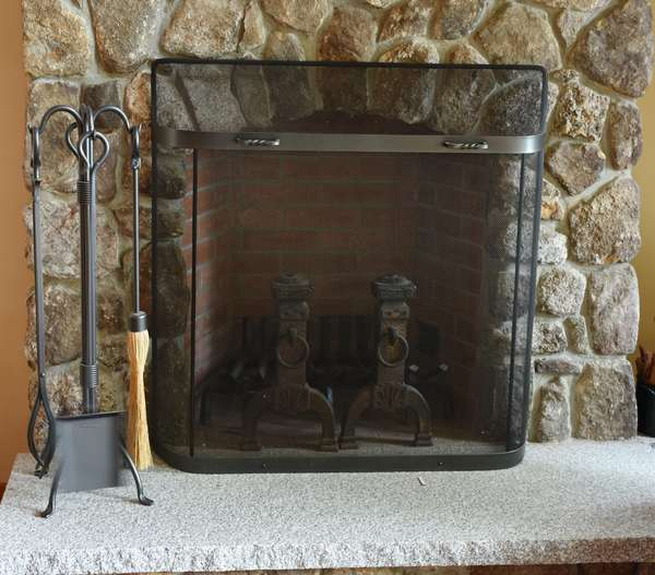 Set of fire hearth items including a pair of andirons, fire screen, and tools