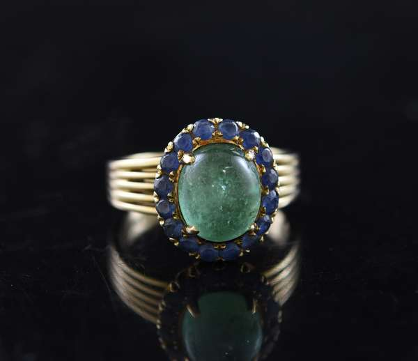 14k yellow gold ring set with oval cabochon emerald, 7.87 mm 9.43 mm, surrounded with 16 round faceted blue sapphires, size 6.5