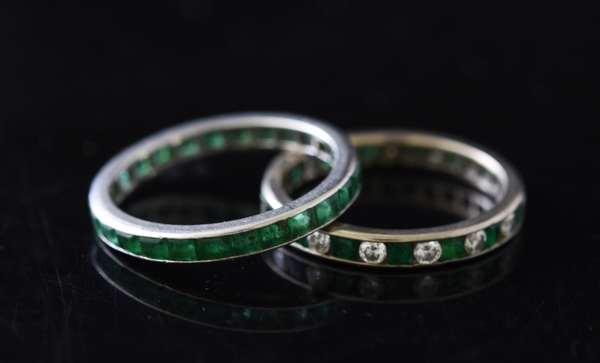 Two platinum bands, one with channel set emeralds other with diamonds and emeralds, size 6.5-7