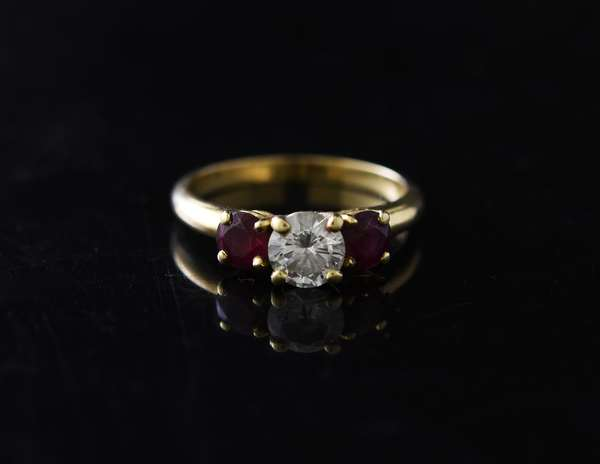 14k yellow gold ladies ring set with approx. .67 ct. round diamond flanked with two red spinels, size 6