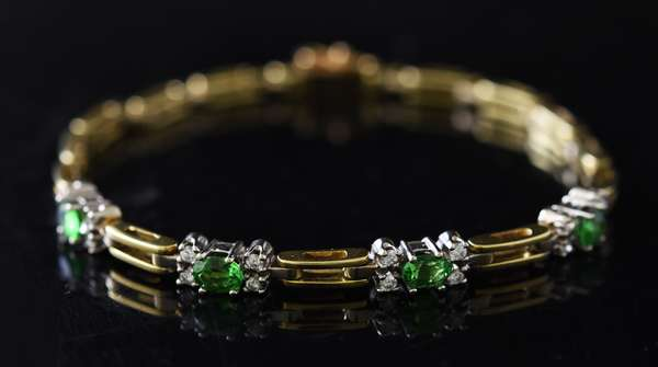 14k yellow gold bracelet set with four green garnets and 16 small diamonds, 7.5