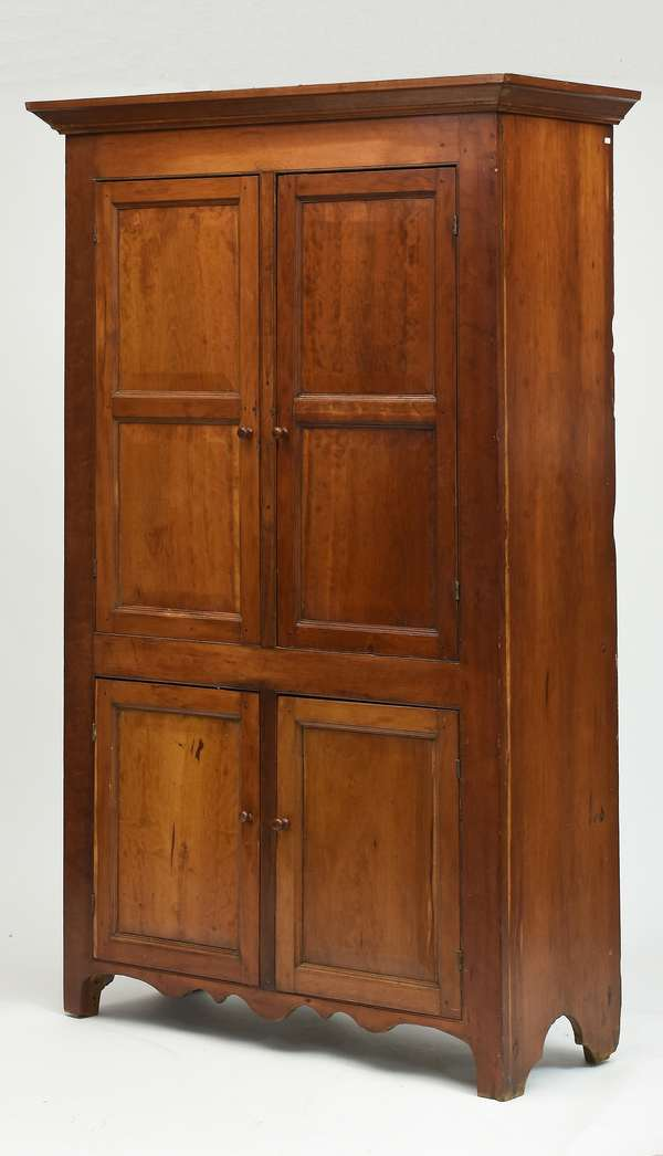Early 19th C. cherry two over two door floor cupboard - raised panels on cut out base with shaped apron, 47