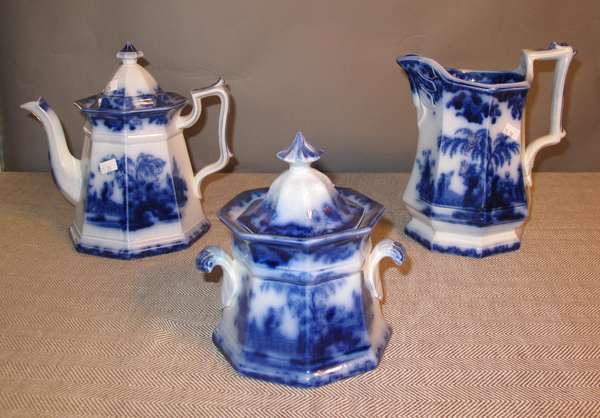 "Three piece Scinde Flow Blue lot, including teapot, pitcher and sugar with lid, 7""H. and 9""H. (75-38)"