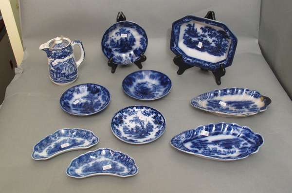 "Two Flow Blue condiment plates 9""D. Two Flow Blue English bone dishes 6½""; Flow Blue serving bowl 8""; English blue and white creamer 6""H; four Flow Blue Scinde sauce dishes 6""D. (75-178)"
