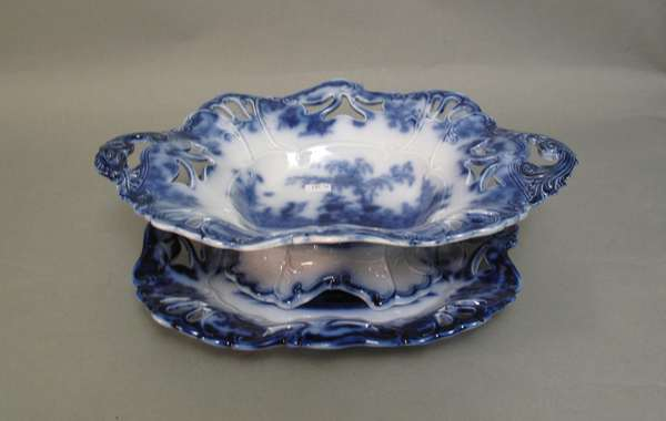 "Shelf #3 of curio cabinet: Scinde Flow Blue serving dish with under-­? plate. 14""L (75-281)"