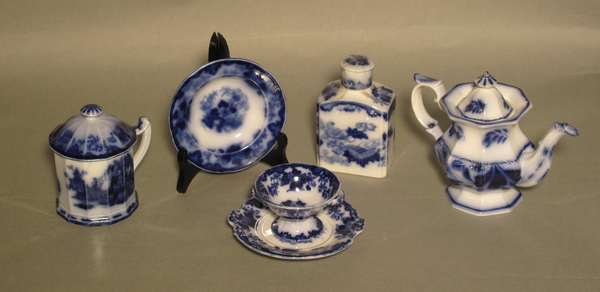 Shelf #3 of curio cabinet: Five pieces of flow Blue Scinde including tea caddy, creamer, covered cup, cup and saucer (75-282)