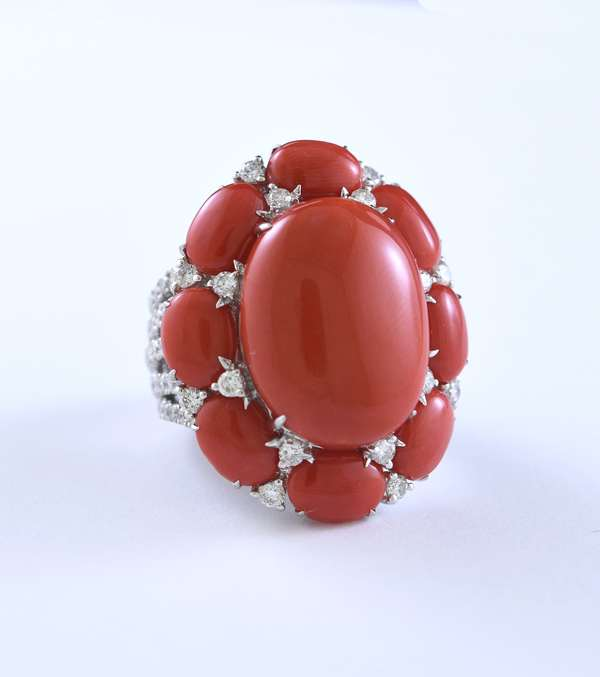 18k white gold diamond and coral cabochon ring set with one 20 x 15 mm center cabochon surrounded by eight, 6 x 8 mm cabs, accented by approx. 1.85 ct total weight round brilliant cut diamonds, size 7.5, 20 grams