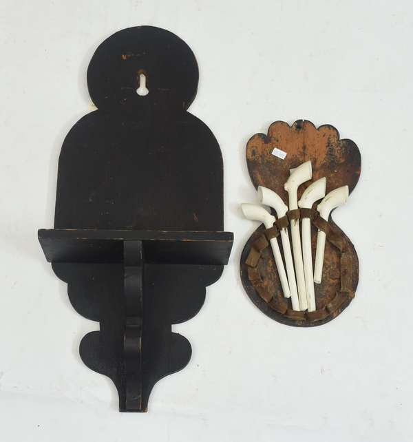 Two early country wall units including a wall shelf in black paint with provenance along with a hanging circular pipe holder, 24