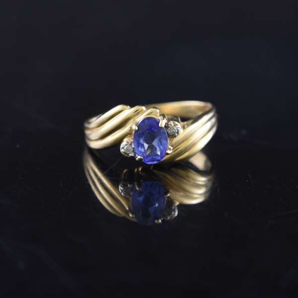Ref 25 - 14k yellow gold ring set with an oval tanzanite measuring 5.04mm x 6.40mm, with two small diamonds, ring size 8, 3.6 grams (96-27)