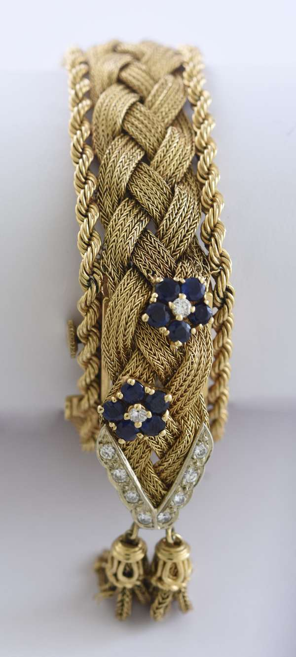 Ladies 14k yellow gold woven bracelet watch with hidden movement, accented by approx. 1.0 ctw round blue sapphires and approx. .35 ctw round brilliant cut diamonds, 6