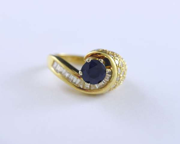 18k yellow gold sapphire and diamond asymmetrical ring, approx. 1.10 ct round blue sapphire accented by 1.15 ctw baguette and round brilliant cut diamonds, size 6, 10.1 grams