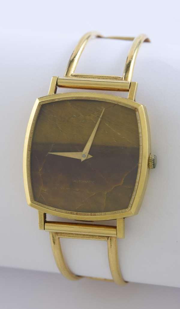 18k yellow gold Bucherer cuff bracelet watch, monogram R.E.L. with a square tiger eye face, 7
